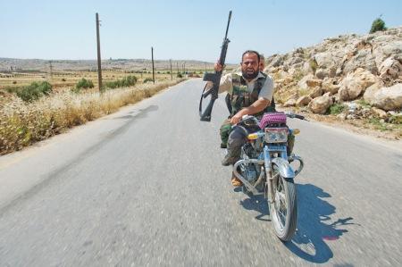 Një kryengritës sirian, pjesëtar i Ushtrisë Çlirimtare të Sirisë gjatë lëvizjes së një kolone para-ushtarake të forgave kryengritëse në provincën Idlib në Republikën Arabe të Sirisë. (Foto: Vedat Xhymshiti, për Der Spiegel)