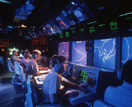 Crew members monitor radar screens in the combat information center aboard the guided missile cruiser USS VINCENNES (CG-49) on January 1, 1988. (Photo/TIM MASTERSON)