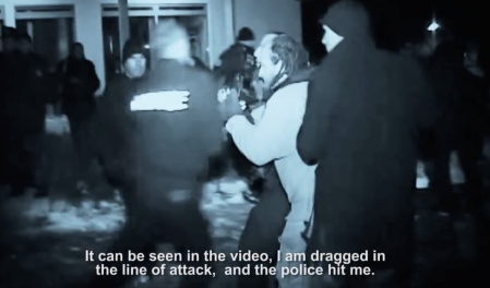 Pre-knocked-out photojournalist Vedat Xhymshiti, bearing a photo-camera on his chest and his PRESS Cards, while another camera has been cast-away during the attack. He is being dragged by more then one other un-identified civilian-clothed person, who deliberately sent him into the target scene. After having knocked him-out the perpetrator's colleagues other Kosovo Police officers into an in-door facility. (PrintScreen Photo)
