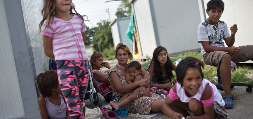 A Roma mother sits surrounded by her children inside the Makis Roma settlement on the outskirts of Belgrade, Serbia, Wednesday, Aug. 19, 2015. (Marko Drobnjakovic)