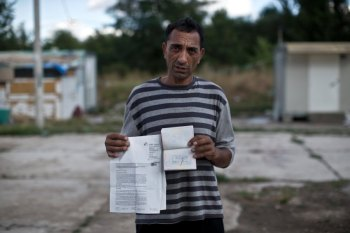 Haljilj Hasani, a Roma minority that was denied asylum in Germany, poses for a portrait as he shows his Serbian passport with a ban to enter Germany stamped on its page, and other documents, at the Makis Roma settlement on the outskirts of Belgrade, Serbia, Tuesday, Aug. 18, 2015. (Marko Drobnjakovic)