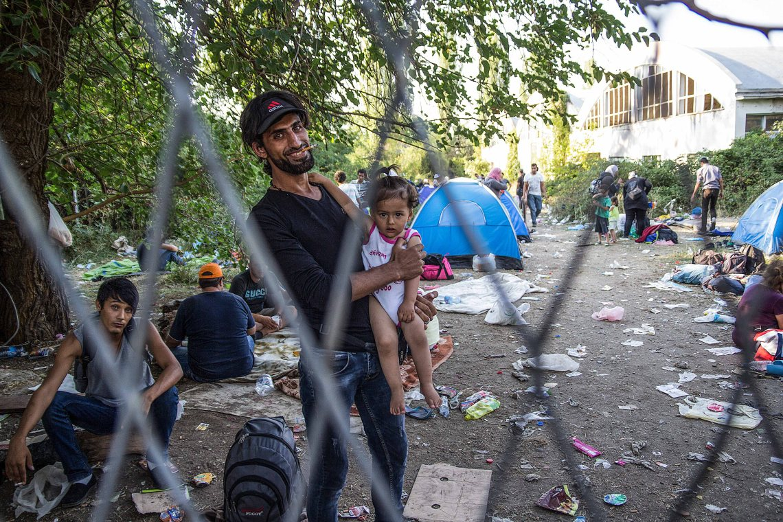 Migrants try to get rest at a makeshift camp in Presevo Valley of Serbia. Over 15,000 migrants, including many women with babies and small children, have crossed into Serbia over the past few days and headed toward Hungary and the EU Schengen Area, a zone with no internal border checks between member countries. (Photo: Krenar Halimi)