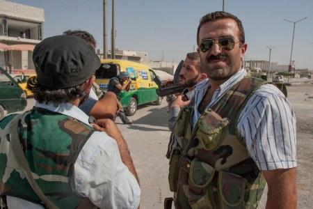 Një luftëtar Kurd, pjesëtar i UÇS-së, bashkë me luftëtarë të tjerë duke patrulluar në rrugët e shkatërruara të qytetit të trazuar verior sirian, Aleppo. [Foto: Vedat Xhymshiti, për Der Spiegel]